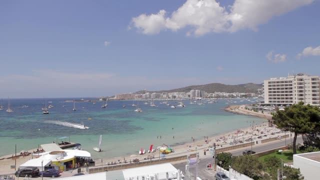 san antonio bay ibiza beach,views from the city to an ibiza beach with boats and cars on a road - formaggio comté video stock e b–roll