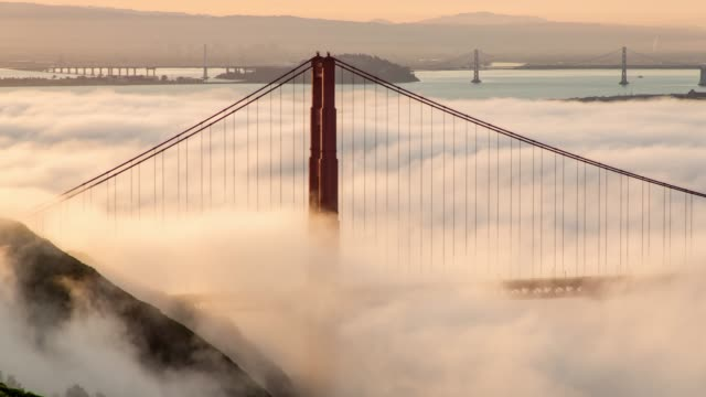 San Francisco Golden Gate Bridge Low Fog Morning Light Rolling Fog under the North Tower of the Golden Gate Bridge with the Bay Bridge in the Background suspension bridge stock videos & royalty-free footage