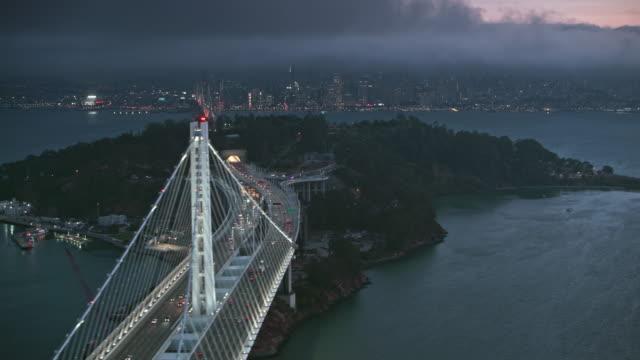 공중 샌 프란 시스 코-오클랜드 베이 브리지와 샌 프란 시스 코의 도시를 내려다 보이는 해질녘 yerba 부에나 섬 - 장엄한 스톡 비디오 및 b-롤 화면