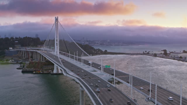 AERIAL San Francisco-Oakland Bay Bridge towards the Yerba Buena Island at sunset
