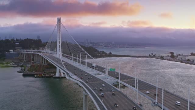 vídeos de stock e filmes b-roll de aerial san francisco-oakland bay bridge towards the yerba buena island at sunset - ponte