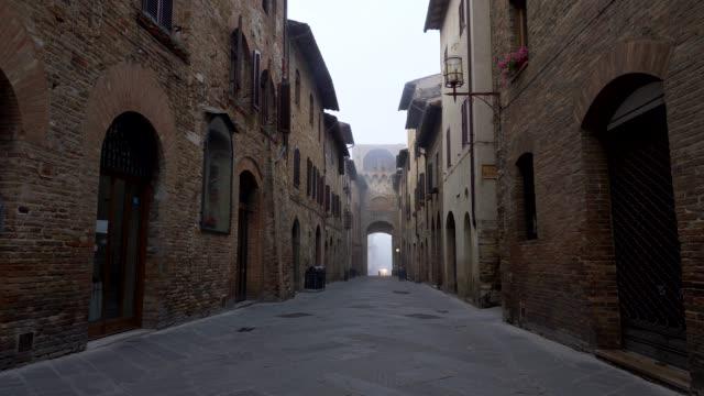 san gimignano, i̇talya. ortaçağ şehrin dar bir sokakta yürürken, aura ile eski kez dolu. caddenin her iki tarafında eski tuğla duvarlı binalar vardır. 4k - toskana stok videoları ve detay görüntü çekimi