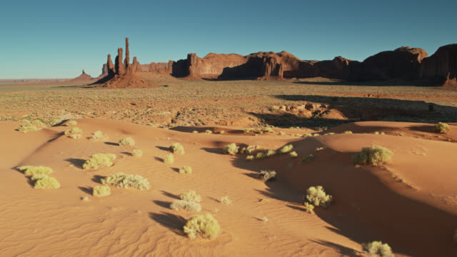 Sand Dunes Around Totem Pole in Monument Valley - Drone Shot