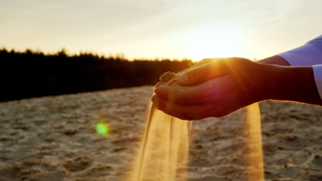 Sand pours from the man's hands at sunset. Concept: the transience of time, changes lifetime. Slow motion video video