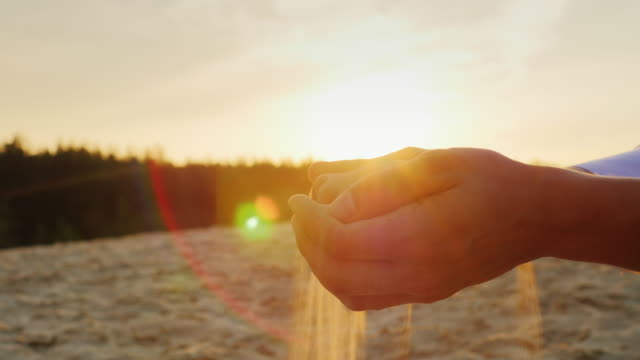 Sand pours from the man's hands at sunset. Concept: the transience of time, changes lifetime video