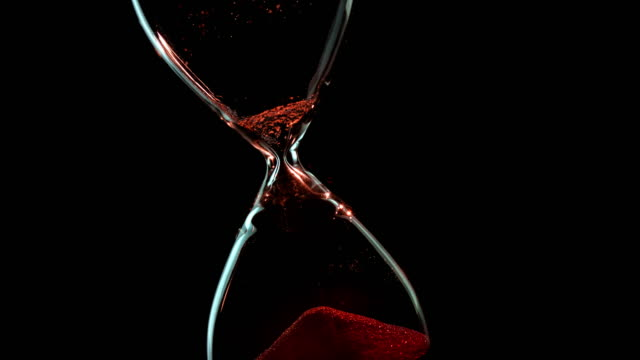 SLO MO LD Sand running in an hourglass against black background