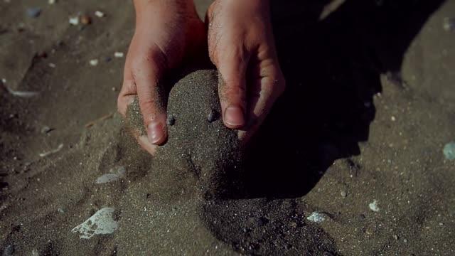vídeos de stock e filmes b-roll de sand running through a womans hands. close ip - mulher deixar ir