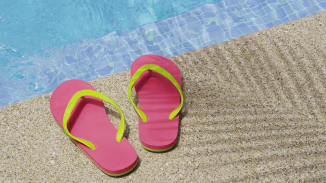 Sandals laying by pool. video