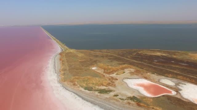 vídeos de stock, filmes e b-roll de antena: restinga entre o azul do mar e lagos de sal - multicóptero
