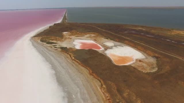 AERIAL: Sandbar between blue sea and salt lakes Futuristic landscape of red salt lake surface with therapeutic mud along shores, aerial video, drone point of view salt flat stock videos & royalty-free footage