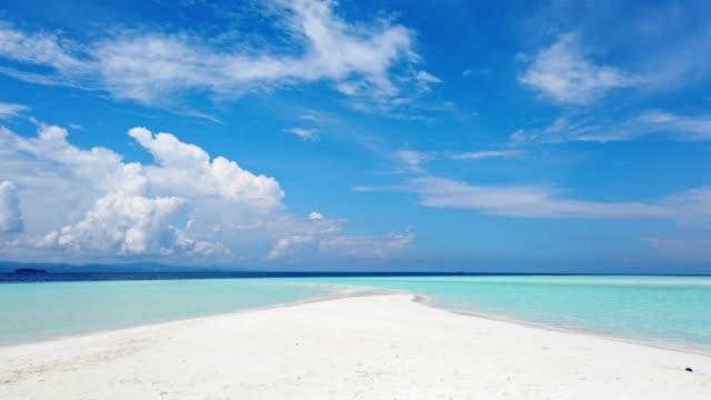 Sandbar left by receding tide with blue sky, seascape in summer time.
