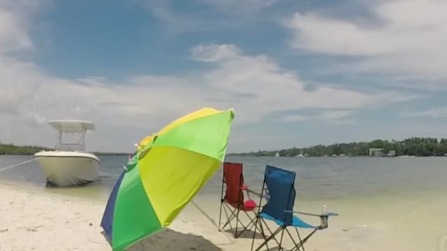 Sandbar with center console boat and beach umbrella with chairs on a sandy island in Jupiter Florida Sandbar with center console boat and beach umbrella with chairs on a sandy island in Jupiter Florida florida us state stock videos & royalty-free footage