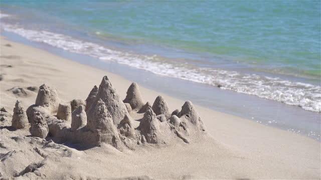 プラスチックの子供のおもちゃと白い熱帯のビーチで砂の城 - 城点の映像素材/bロール