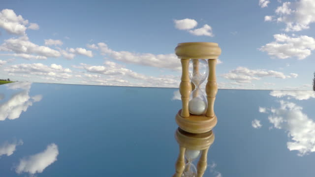 sandglass on mirror and clouds motion, Time concept, timelapse video