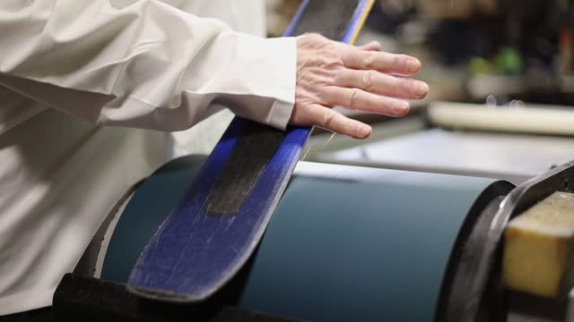 sanding base in ski rental and repair shop in various stages of production series - negozio sci video stock e b–roll
