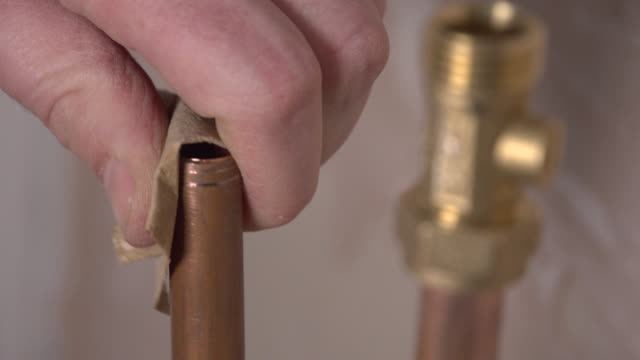 sanding down old copper pipe to install a new joint. Closeup pluming shot