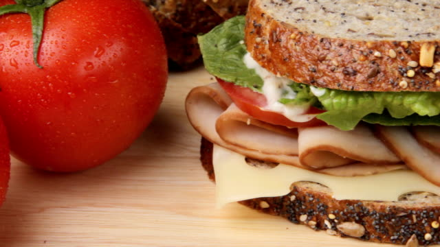 Sandwich Close up camera pan of fresh vine ripe tomatoes, turkey sandwich on cutting board, shot in HD video turkey stock videos & royalty-free footage
