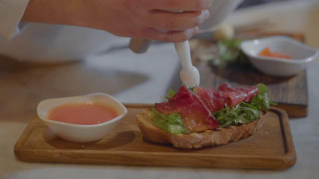 Sandwich with arugula and salted salmon is cooking in restaurant close up.