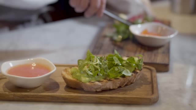 Sandwich with arugula is cooking in restaurant close up.