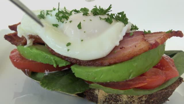 blt-sandwich mit avocado und pochiertem ei. serviert auf rustikalen handwerker vollkornbrot konfrontiert - portion stock-videos und b-roll-filmmaterial