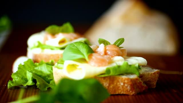 smörgås med ost, salladsblad och rödfisk på trä - cheese sandwich bildbanksvideor och videomaterial från bakom kulisserna