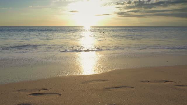 vídeos y material grabado en eventos de stock de playa de arena con huellas y grandes olas espumosas con gente - borde del agua