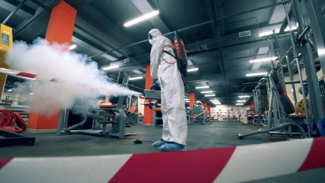 Sanitary inspector is fumigating fitness machines in the gym video