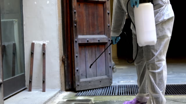 Sanitation worker is disinfecting the entrance of an office before the reopening video