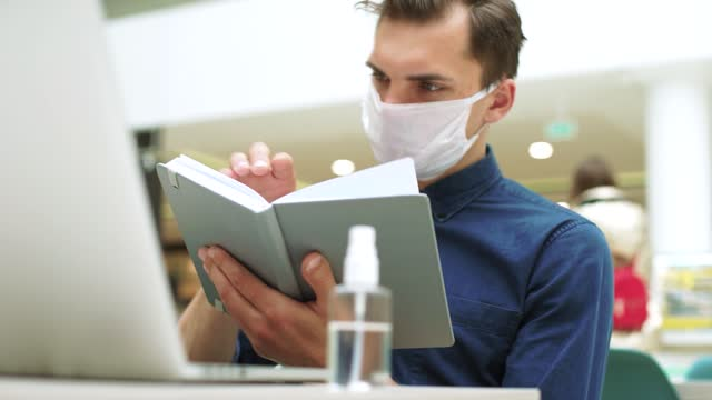sanitizer spray on the table in front of a young man reading a book