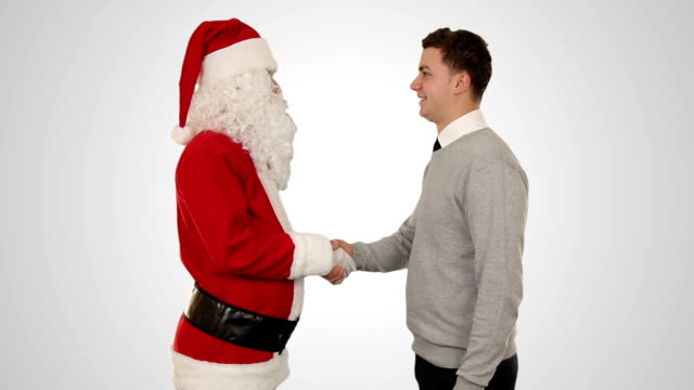 Santa Claus and Young Businessman against white, shaking hands video