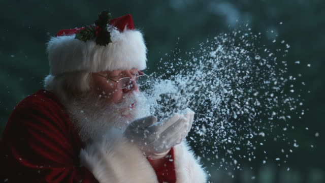 vídeos de stock e filmes b-roll de santa claus blowing snow from hands in slow motion - pai natal