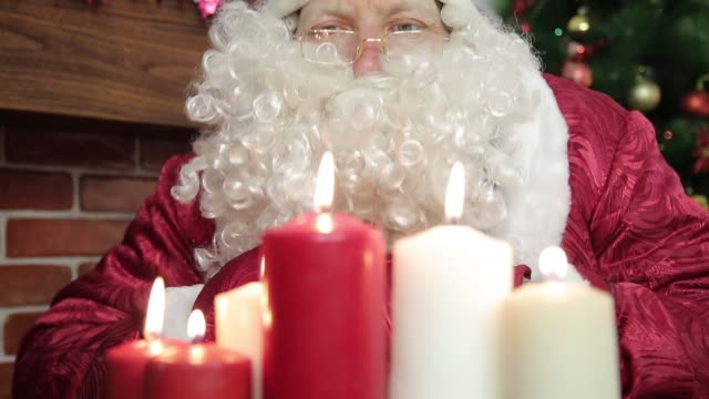 Santa Claus blows out the candles. video