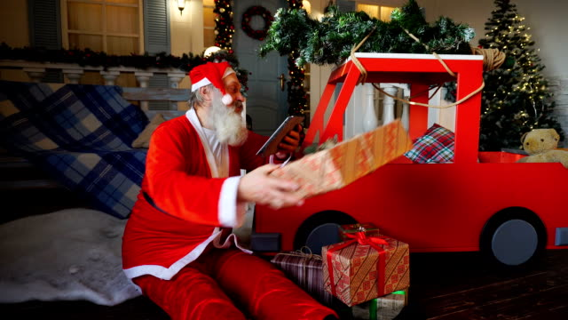 Santa Claus checking list of presents on tablet and putting gifts into car video