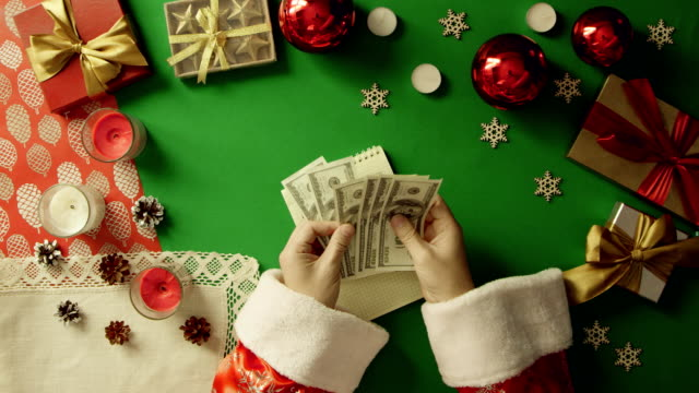 Santa Claus counting his money over notebook with expenses writings by Christmas table with chroma key, top down shot video