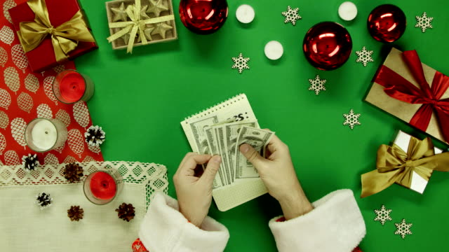 Santa Claus counting his money over notebook with expenses writings by Xmas table with chroma key, top down shot video