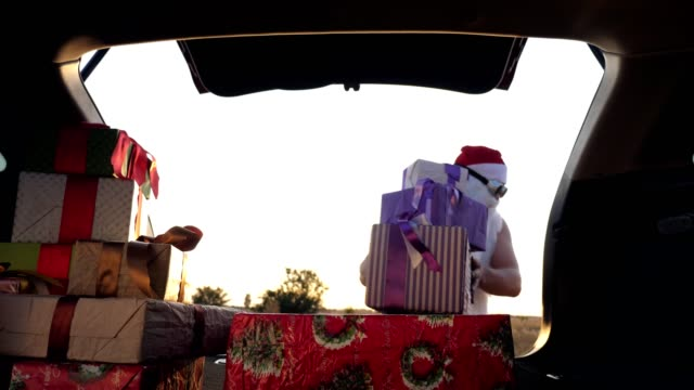 santa claus delivering gifts. gifts from santa. delivery service. deliveryman unloads boxes. gift boxes in car. beautifully wrapped parcels. view from inside the car. donation, charity or delivery concept video