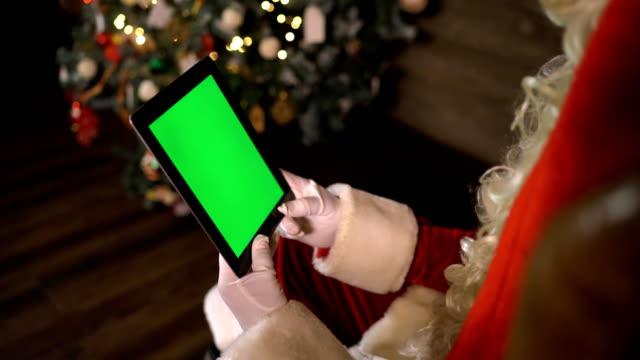 santa claus digitalen schreibblock grüner bildschirm - weihnachtskarte stock-videos und b-roll-filmmaterial