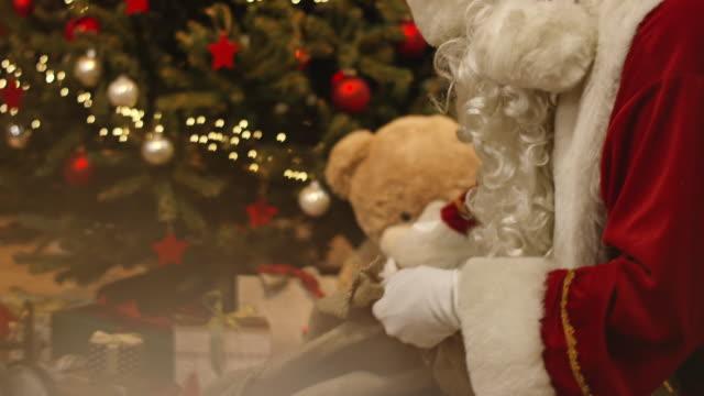 santa claus distributing presents under the christmas tree - santa bildbanksvideor och videomaterial från bakom kulisserna
