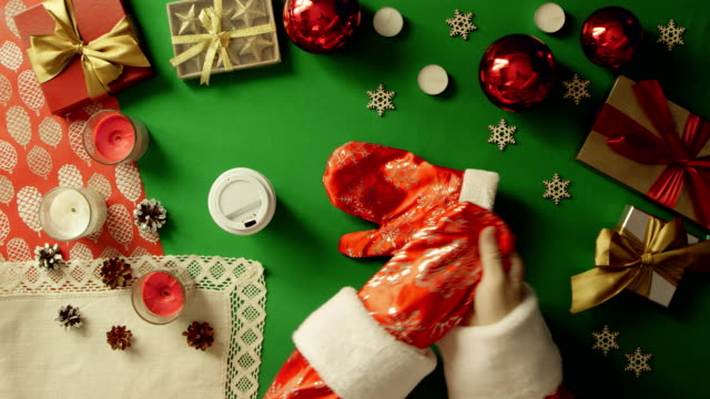 Santa Claus drinks coffee by Christmas wooden table on table with chroma key video