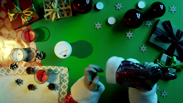 Santa Claus drinks coffee by New Year wooden table on table with chroma key video