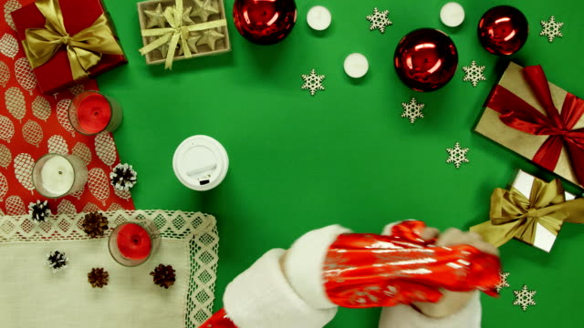 Santa Claus drinks coffee by Xmas wooden table on table with chroma key video