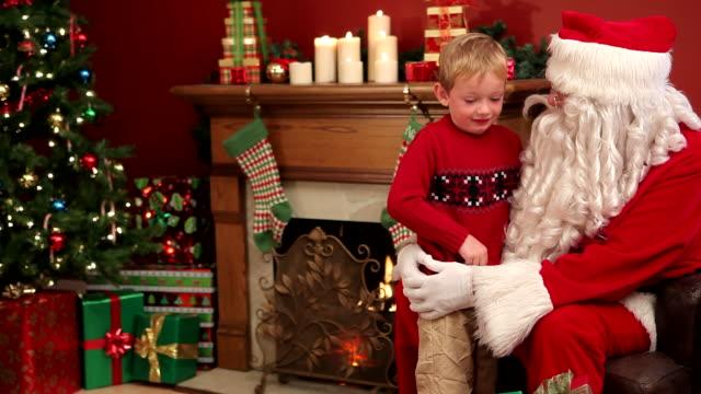 weihnachtsmann, die geschenke für jungen - weihnachtsstrumpf stock-videos und b-roll-filmmaterial