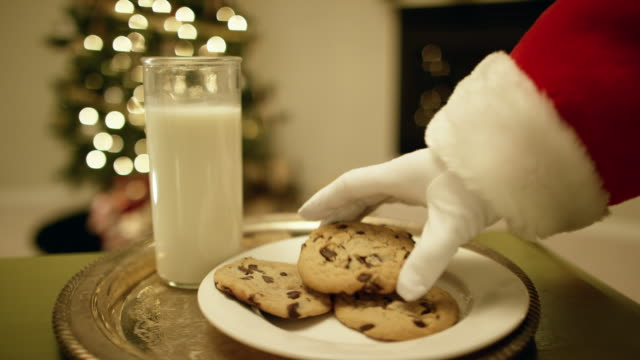 vídeos de stock e filmes b-roll de santa claus' gloved hand picks up a chocolate chip cookie from a tray with a glass of milk on it with a christmas tree and a fireplace in the background on christmas eve - christmas cookies