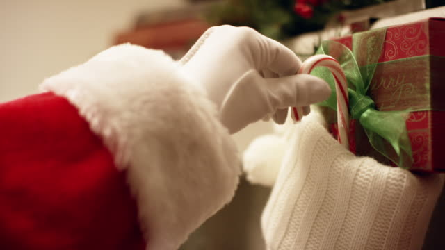 Santa Claus' Gloved Hand Places a Red and White Striped Candy Cane in a Christmas Stocking Hanging from a Mantel on Christmas Eve