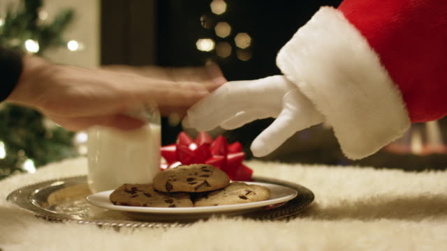 vídeos de stock e filmes b-roll de santa claus' gloved hand tries to pick up a chocolate chip cookie from a tray with a glass of milk on it but a hand swats it away with a christmas tree and a fireplace in the background on christmas eve - christmas cookies