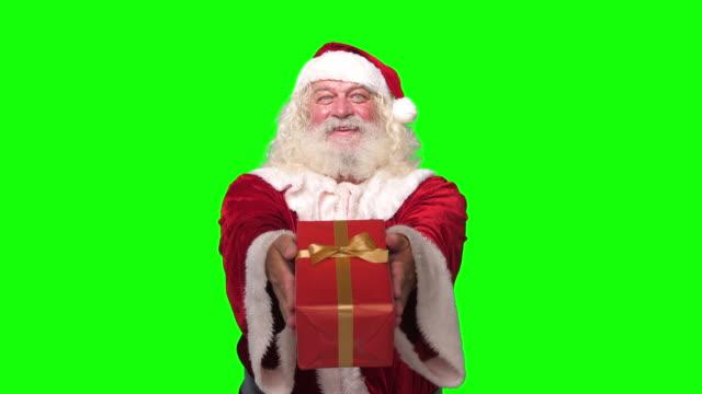 vídeos de stock e filmes b-roll de santa claus handing christmas present gift at camera smiling in front of chroma key green screen background - christmas card