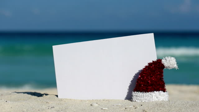 Santa Claus Hat and white blank placard at sandy beach on caribbean sea video
