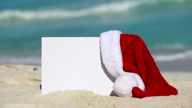 砂浜でサンタ クロースの帽子と白の空白のプラカード - サンタの帽子点の映像素材/bロール