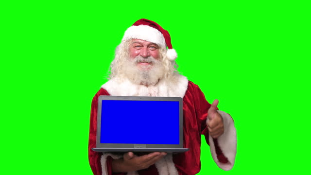 vídeos de stock e filmes b-roll de santa claus holding a laptop with blue screen pointing at it chroma key green screen background - pai natal