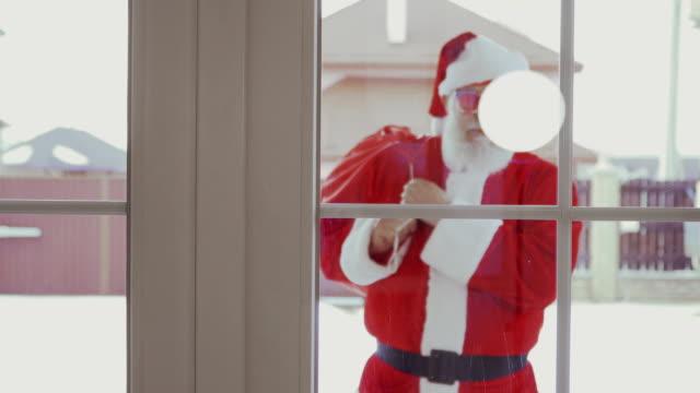 stockvideo's en b-roll-footage met santa claus in grappige zonnebril komen in huis - raam bezoek